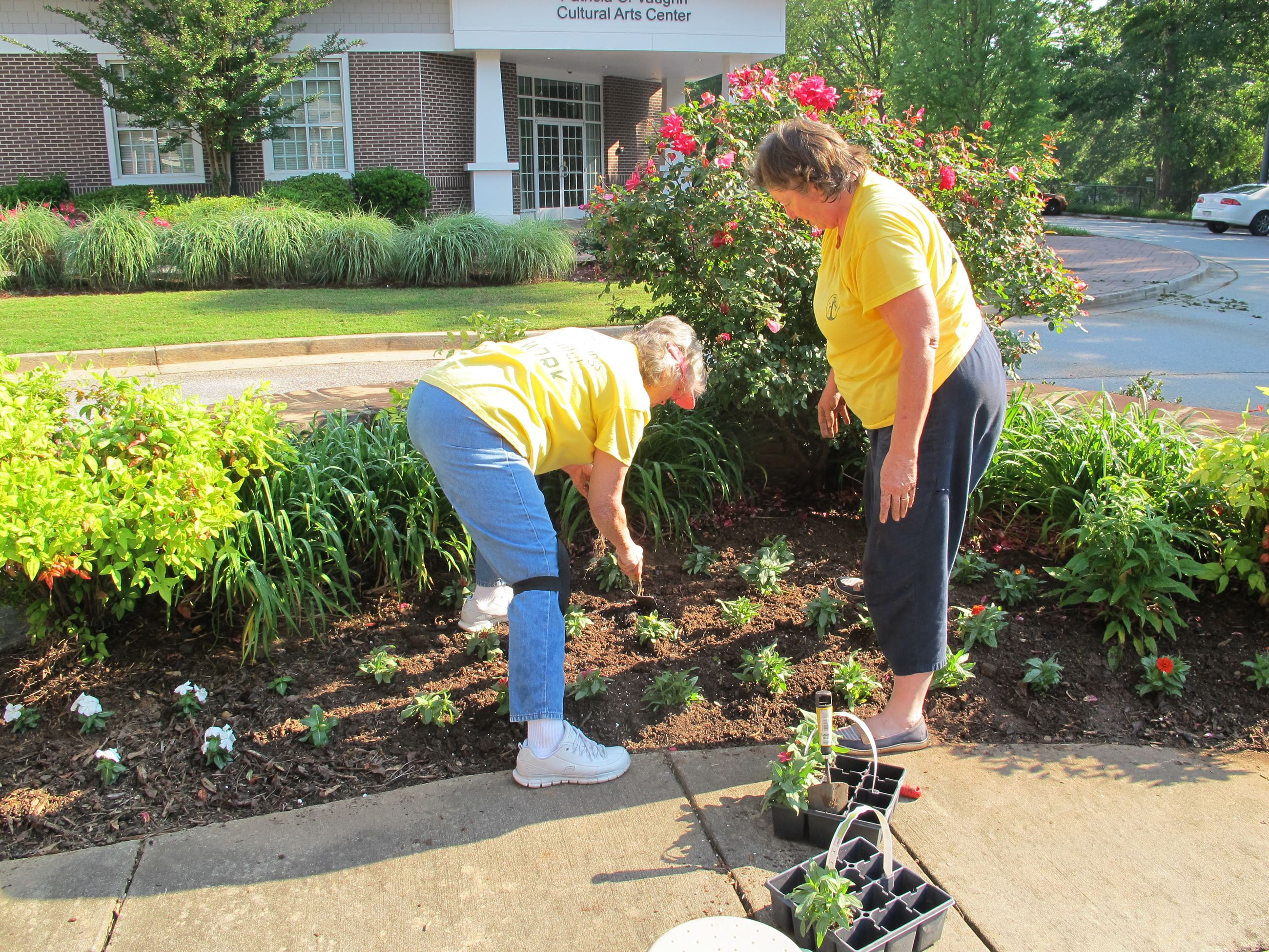 Two volunteers planting flowers at the Ford Center.